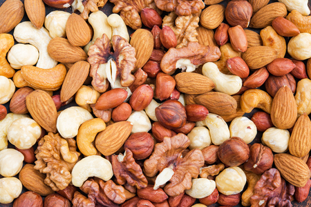 Top view of tasty mix nuts background. Concept healthy snack. Imagens