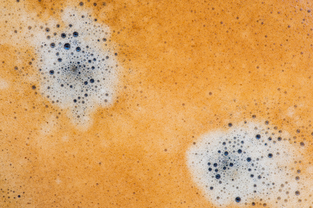 Black coffee crema foam texture.
