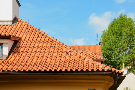 Red ceramic shingles roof with attic windows and chimney against blue sky. Decorative rain gutter. Imagens