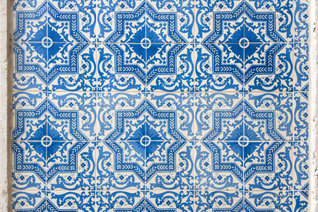 Old wall with traditional Portuguese decor tiles azulezhu in blue tones.