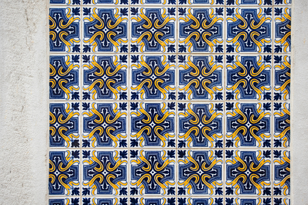 Old wall with traditional Portuguese decor tiles azulezhu in blue and yellow tones.