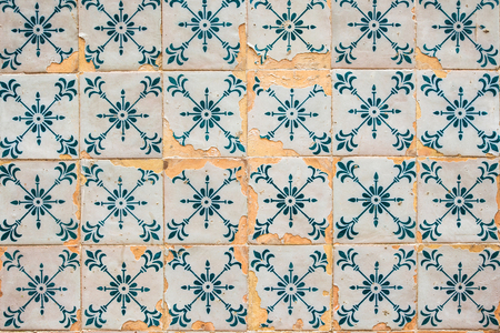 Old cracked wall with traditional Portuguese decor tiles azulezhu in blue tones.