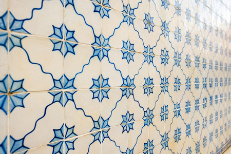 Old wall with traditional Portuguese decor tiles azulezhu in blue tones on a beige background.