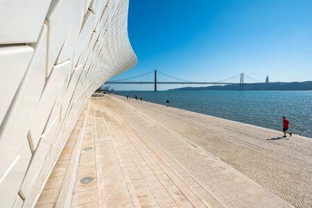 LISBON, PORTUGAL - FEBRUARY 12, 2019: People walk near famous MAAT Museum in Lisbon near river Tagus and Landmark 25 of April bridge. Editorial
