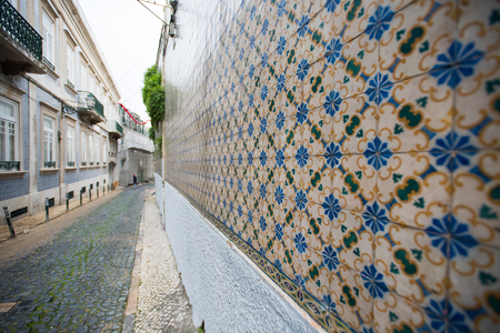 European street with old wall with traditional Portuguese decor tiles azulezhu in blue,yellow and brown tones.