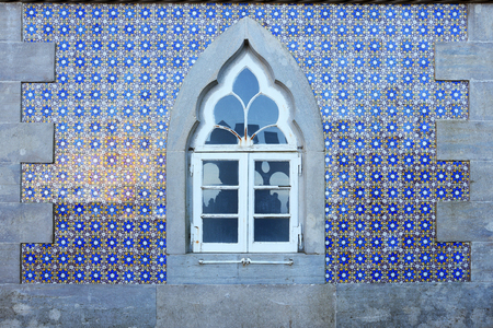 Old wall with traditional Portuguese decor tiles azulezhu in blue,yellow and brown tones with an old window as background.