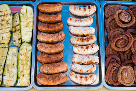 Grilled sausages and vegetables are sold on the fair.