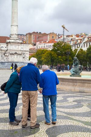 LISBON, PORTUGAL - FEBRUARY 10, 2019: Adults tourists look to the map on the Square Dom Pedro. Banco de Imagens - 137905049