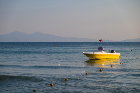 Empty rescue yellow boat with the flag of Turkey to the sea on the background of the rocky coast under the blue sky. Imagens