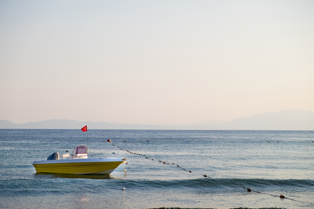 Empty rescue boat with the flag of Turkey to the sea on the background of the rocky coast under the blue sky.