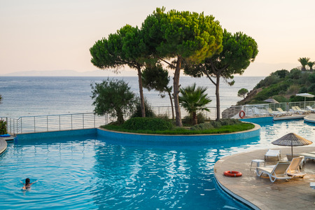 Large modern swimming pool with sun loungers and pine trees against the backdrop of the sea.