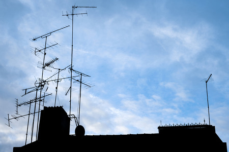 Silhouette of many different antennas on the rooftop against blue sky.