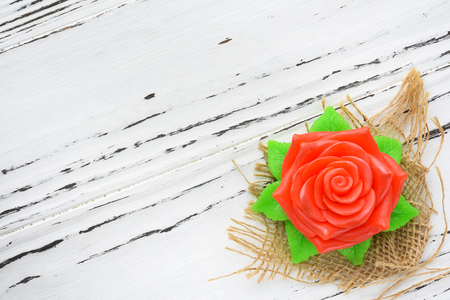 Natural soap in the shape of a rose on wooden background. Spa and aromatherapy.