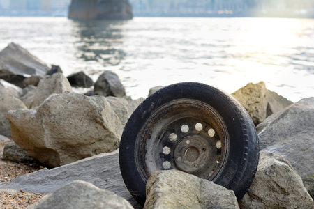 Abandoned used tyre on coastline. The problem of recycling waste, garbage, environmental pollution. Car tire thrown on the beach. Stockfoto
