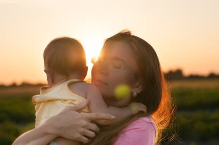 Cute baby in the arms of a happy mother in the rays of the setting sun. The concept of a good family. Stockfoto