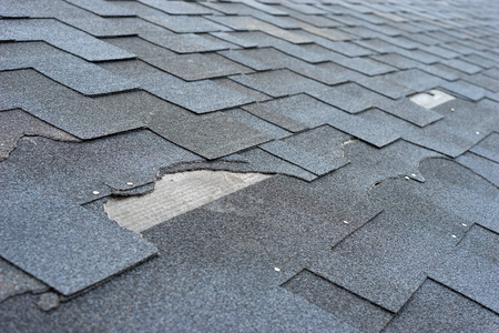 Ð¡lose up view of asphalt shingles roof damage that needs repair.