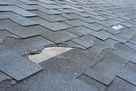 Ð¡Cierre de vista el daño del techo de tejas de asfalto que necesita reparación. Foto de archivo