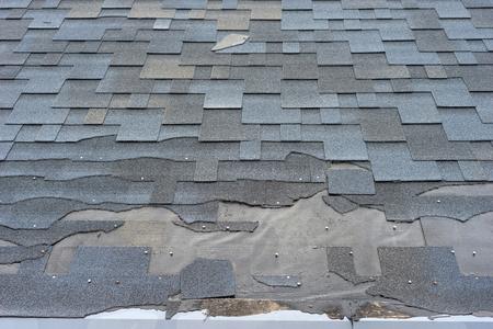 Ð¡lose up view of bitumen shingles roof damage that needs repair. Stockfoto