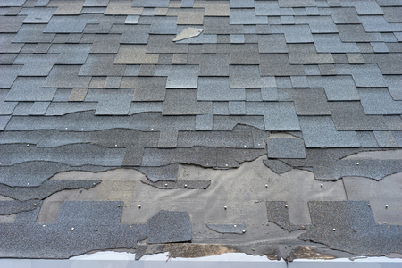 Ð¡lose up view of bitumen shingles roof damage that needs repair. 版權商用圖片 - 125361727