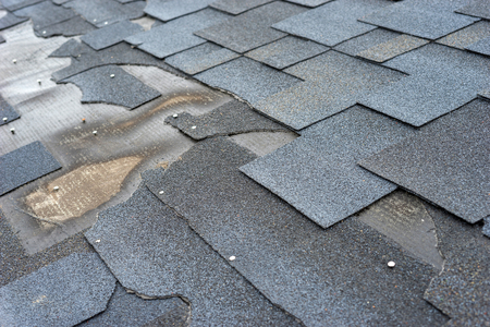 �¡lose up view of bitumen shingles roof damage that needs repair.