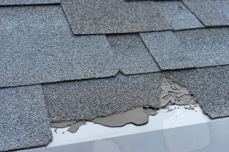 Ð¡loseup view of asphalt shingles roof damage that needs repair.