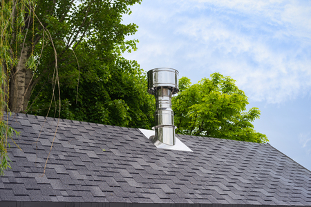 Close up view on bitumen asphalt roofing shingles and stainless steel chimney pipe. Stockfoto