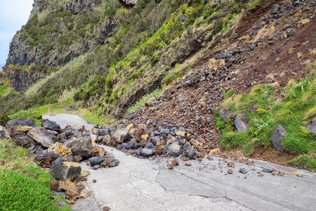 La pendiente de piedra de deslizamiento de tierra de montaña de peligro amenaza con bloquear la carretera para el conductor y el residente de la ciudad.