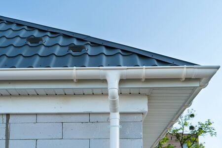 New metal tile roof with white rain gutter. SIP panel house construction. Unfinished building.