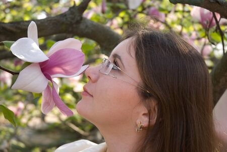 Pretty girl sniffing a pink magnolia flower. Stockfoto