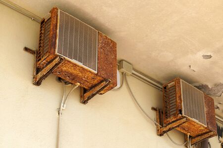 Old rusty air conditioner requiring repair or replacement outdoor unit. An example of the influence of air and climate control.