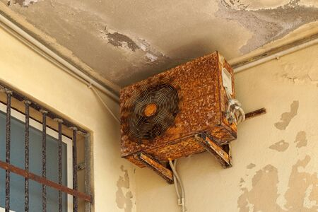 Old rusty air conditioner requiring repair or replacement outdoor unit. An example of the influence of water and climate.