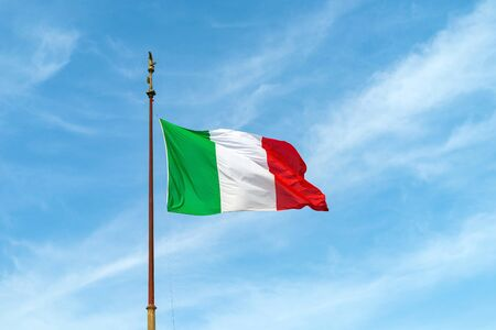 Flag of Italy on the flagpole fluttering in the wind against the blue sky.