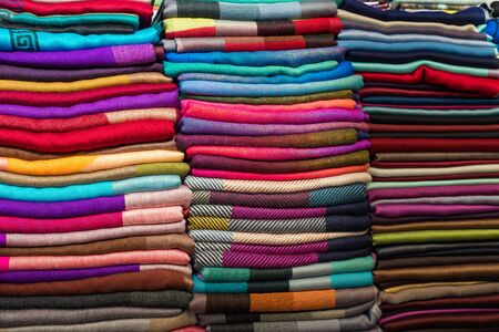 Colorful scarves or shawls for sale at market or fair. Colored fabric background.