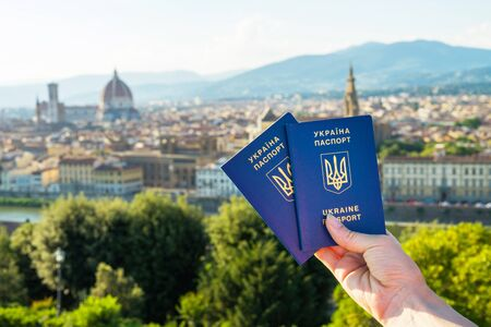 Ukrainian blue biometric passport with identification chip on against Florence background.