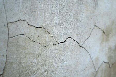 Old foundation and plaster wall with cracks. Building requiring repair closeup. Stock fotó