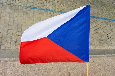 Flag of the Czech Republic on the building on the background of the sidewalk.