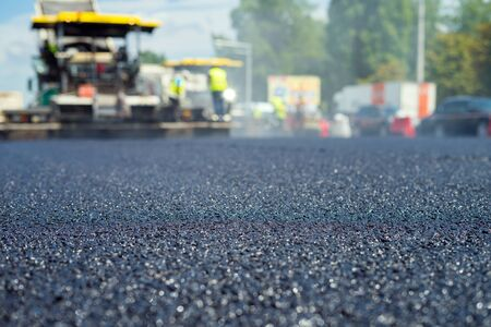 Close up view on the new asphalt road on which special equipment is working. Blurred photo of construction site.