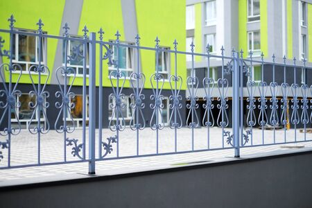 Image of a new decorative metal wrought fence with artistic forging against new modern house.