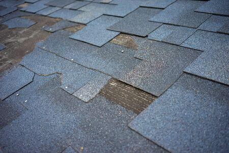 Ð¡lose up view of bitumen shingles roof damage that needs repair.
