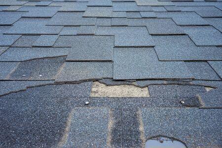 ?lose up view of bitumen shingles roof damage that needs repair.