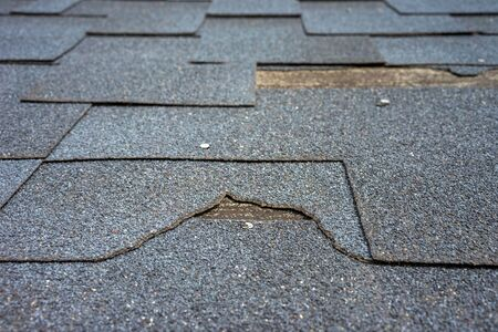 ?lose up view of bitumen shingles roof damage that needs repair.