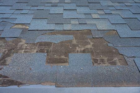 Close up view of bitumen shingles roof damage that needs repair. Stock fotó
