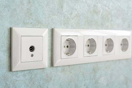 Installation of modern power and television sockets on a wall close-up. Stock fotó