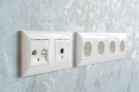 Installation of modern power, communication LAN RJ45 and television sockets on a wall close-up.