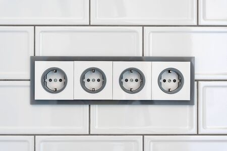 Installation modern sockets on a tile wall close-up. Grey and white electrical outlet.