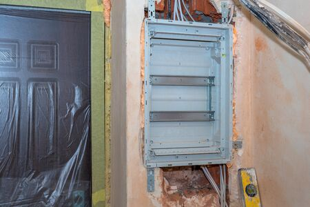 Installation of the voltage switchboard in the wall before the complete assembly. Electrical background.