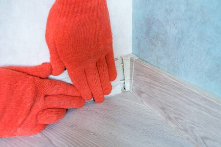 Workers hands Instal plastic skirting board on laminate flooring. Renovation of baseboard at home. Stock fotó