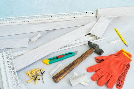 Tools to instal plastic skirting board on laminate flooring. Renovation of baseboard at home.