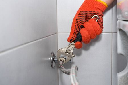 Plumber installs of a toilet hose in a hard-to-reach place with an adjustable wrench. Stock fotó
