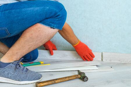 Worker instal plastic skirting board on laminate flooring. Renovation of baseboard at home. Stock fotó